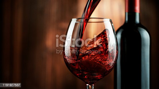 Detail of pouring red wine into glass, dark wooden background. Free space for text