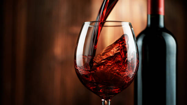 Detail of pouring red wine into glass Detail of pouring red wine into glass, dark wooden background. Free space for text red wine stock pictures, royalty-free photos & images