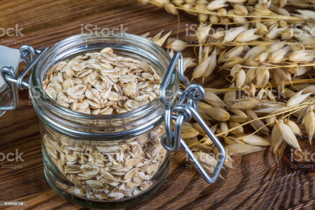 Detail of rolled oats and natural oat on brown wooden background stock photo