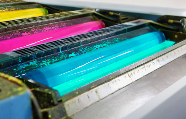 Detail of rollers in offset printing machine Detail of rollers with cyan, magenta and yellow colors (CMYK) in the offset printing machine cmyk stock pictures, royalty-free photos & images