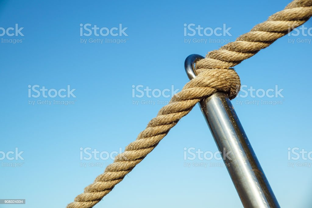 Detail of rope railing of beach walkway, old metal pole, seaside vacation, tranquility, relaxation, stock photo