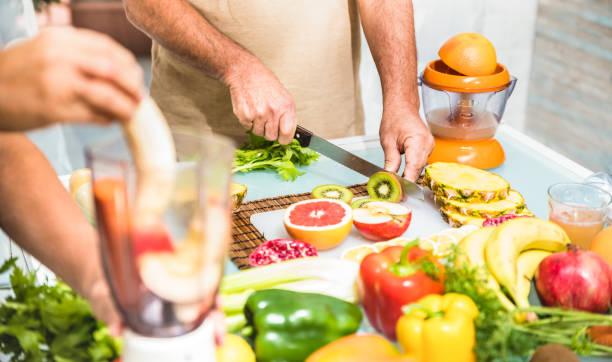 detail der älteres paar in küche mit gesunden lebensmitteln - rentner zu hause vorbereiten blended zentrifuge smoothie mit bio-obst und gemüse kochen - glücklich ältere konzept mit reife rentnerin - low carb süßigkeiten stock-fotos und bilder