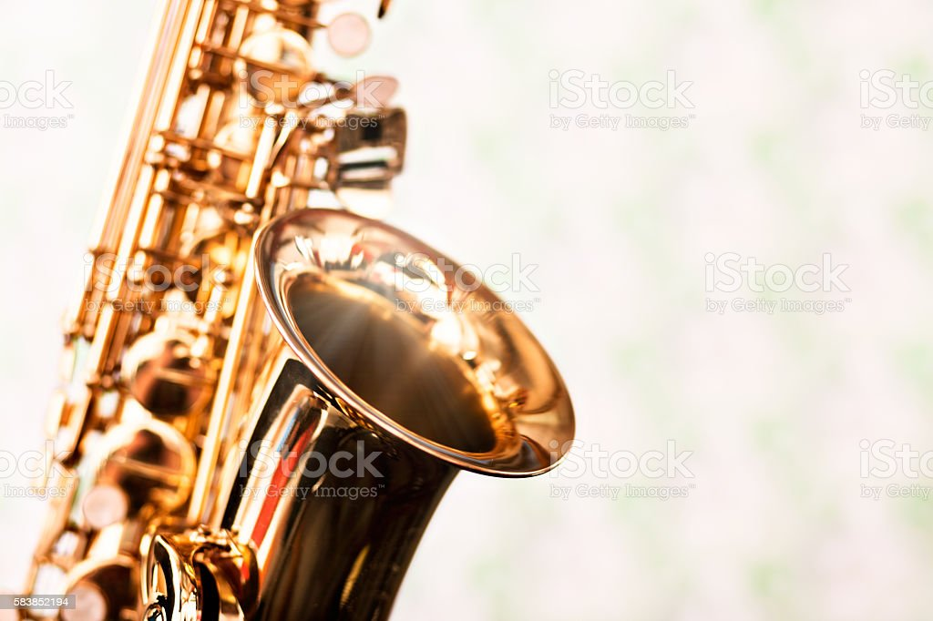 Detail of shining golden alto saxophone on pale, defocused background stock photo