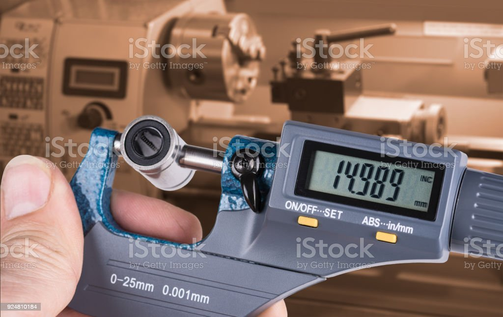 Detail of skilled worker's hand with digital micrometer screw gauge and linear bearing stock photo