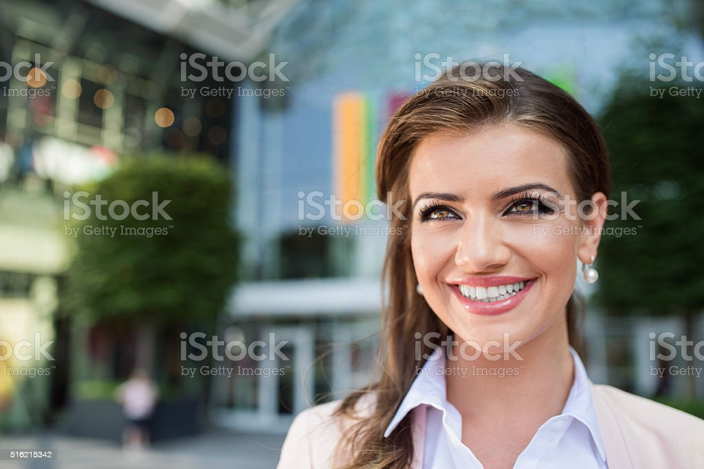 Detail of smiling businesswoman against glassy modern office bui stock photo
