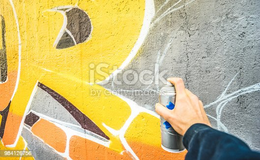istock Detail of street artist painting colorful graffiti on public wall - Modern art concept with urban guy drawing live murales with multi color aerosol spray - Vintage filter with focus on yellow paint 984126756