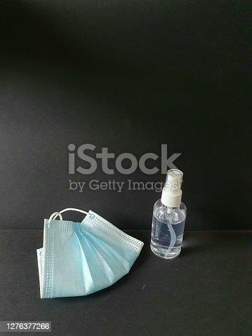 Detail of surgical mask and hydroalcoholic gel.  Background for themes of protection against viruses, diseases and pandemics.