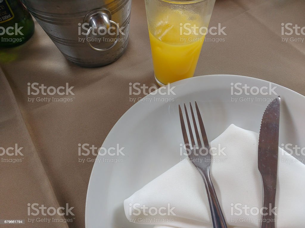 Detail of table with plate, cutlery and napkin stock photo