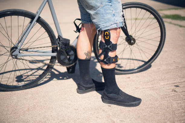 Detail of tattooed man with bicycle wearing a knee bandage after cruciate ligament surgery stock photo