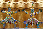 Two figurines carrying the weight of the temple on their shoulders