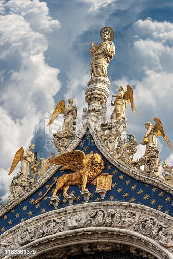 Venice, detail of the Basilica of San Marco with the statue of St Mark the evangelist, golden winged lion and angels. UNESCO world heritage site, Veneto, Italy, Europe