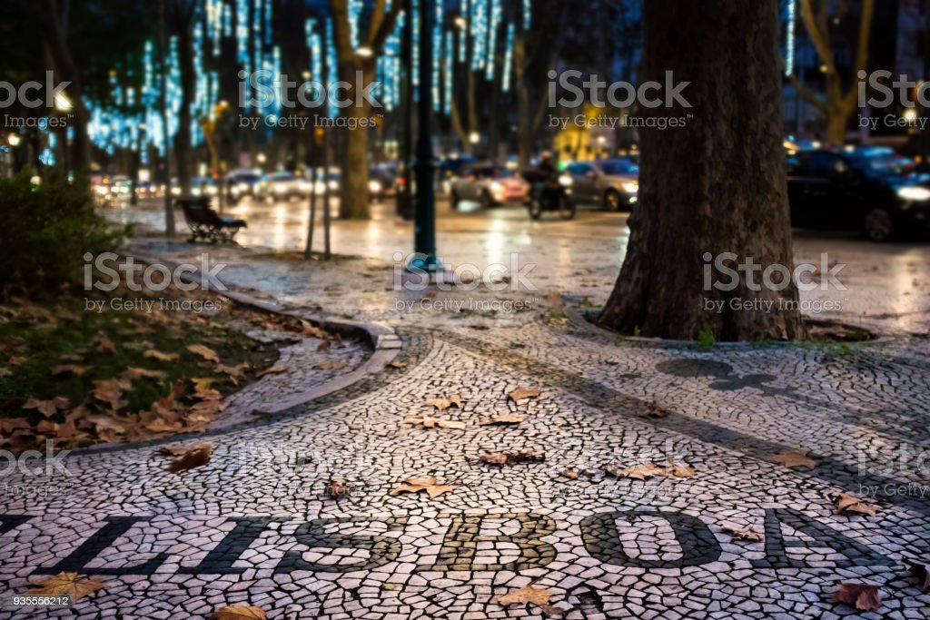 Detail of the beautiful Portuguese pavement at the Liberdade Avenue in the city of Lisbon, Portugal, with dry leaves stock photo