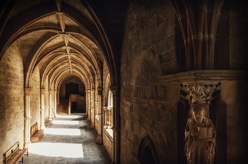 Evora, Portugal, February 1, 2019: Detail of the medieval gothic cloisters of the cathedral of Evora, main city of the Alentejo region (Portugal) with an evangelist statue holding the bible on february 1, 2019