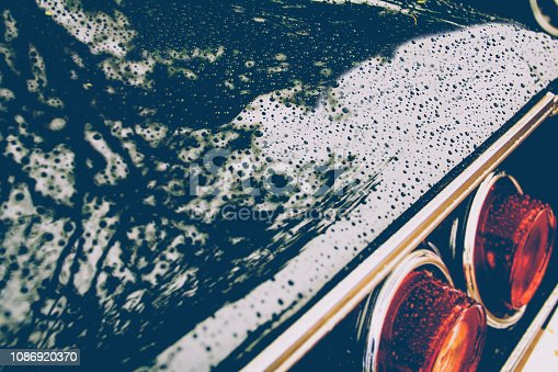 Detail of the rear headlights of a black classic car. Vintage style. Selective focus.