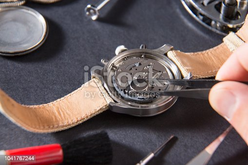 istock Detail of the work of a watchmaker who replaces a battery 1041767244