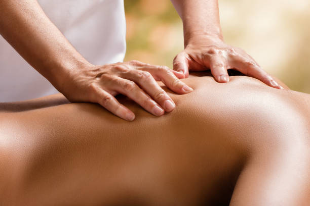 detail of therapist hands on female back. - osteopathy stock pictures, royalty-free photos & images