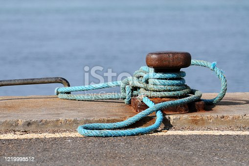 Detail of thick ship ropes tied to an old rusty bollard. Bite d'amarrage with sea in background.