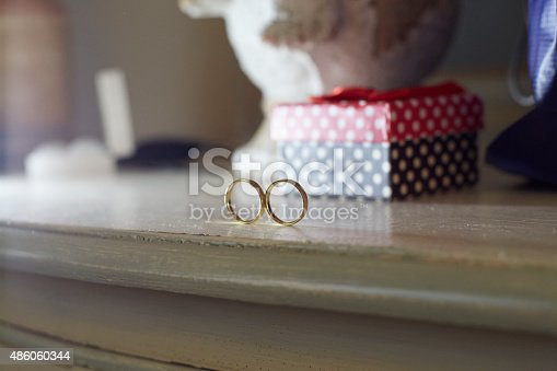 Detail of two gold wedding rings on a wodden table. In the background there is a polka dots red, white and black box. Only the engagement rings are on focus to attract all the attention. Horizontal format. Shot with Canon EOS 5D.