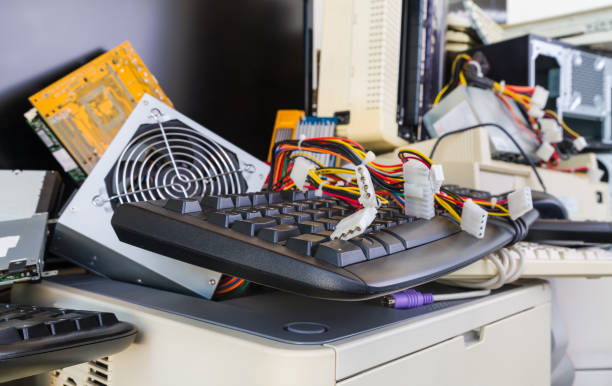 Detail of used hardware components on e-waste pile. Computer printer, case, fan or mainboard with circuit board. Refuse sorting and disposal stock photo