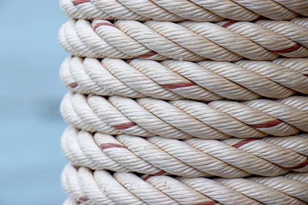 detail of white ship rope wrapped around the pole at fishing port, pattern background stock photo