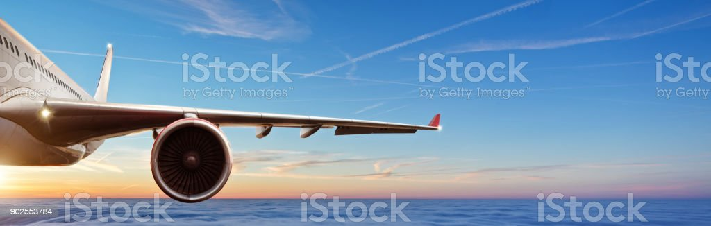 Detail of wing of commercial airplane jetliner flying above clouds in beautiful sunset light. stock photo