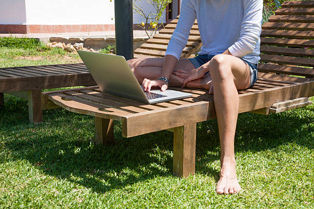 detail of woman using laptop on lounge chair stock photo