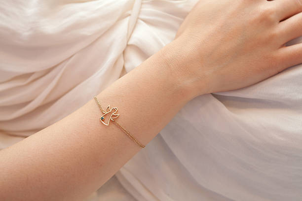 detail der weiblichen seite mit angel-armband - schmuck engel stock-fotos und bilder