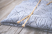 Detail of woven handicraft knit woolen design texture and knitting bamboo needle. Rustic wooden background