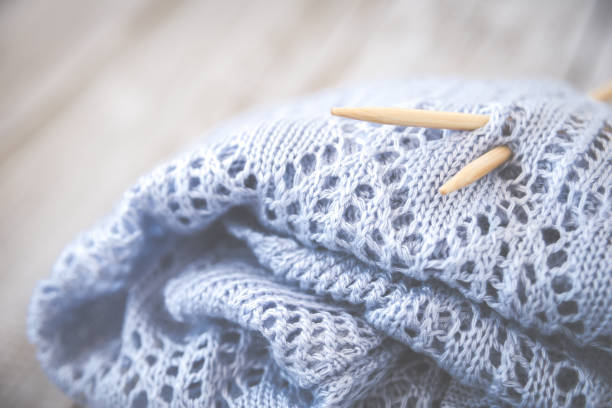 Detail of woven handicraft knit woolen design texture and knitting bamboo needle. Toned retro. Rustic wooden background. stock photo