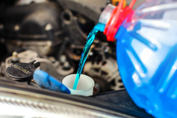 Detail on antifreeze car screen wash liquid pouring into dirty car from blue and red anti freeze water container. stock photo