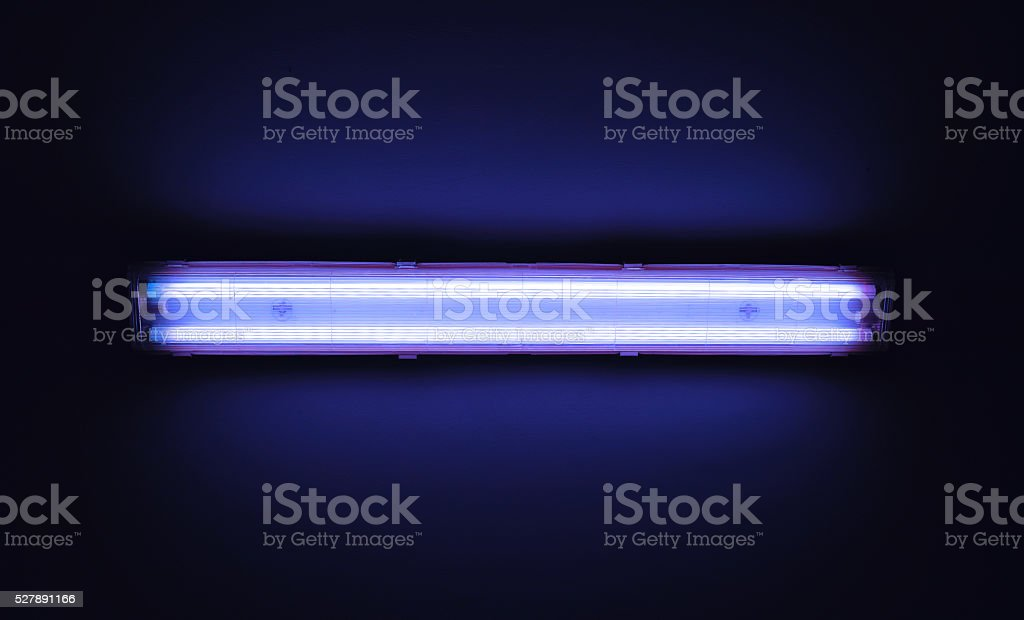 Detail shot of a fluorescent light tube on a wall. stock photo
