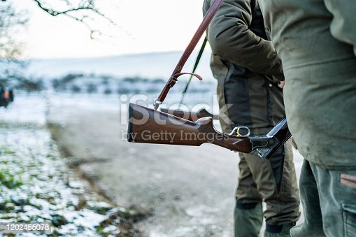Detail view of hunters rifle. Hunter / gamekeeper in a field during winter day.