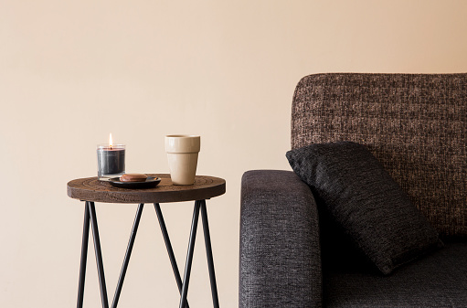 Detail view of modern round wood metal coffee table with cappuccino mug, glass candle burning by the side of sofa.