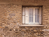 Old white window with white shutters on an old stone wall background