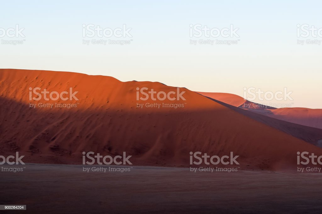 Detail view of red sand dunes in Sossusvlei near Sesriem in famous Namib Desert in Namibia, Africa. Sossusvlei is a popular tourist destination, the dunes are amongst the highest in the world. stock photo