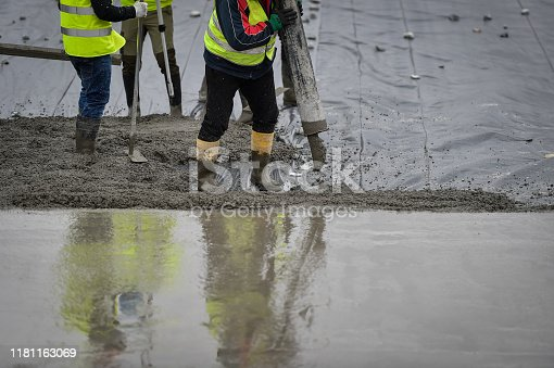 Detail with team of workers pouring concrete on a construction site.