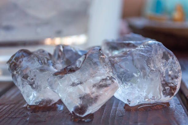 detailed ,close up view of ice cubes on wood table, to defrost, effect of shadows - defrost stock pictures, royalty-free photos & images