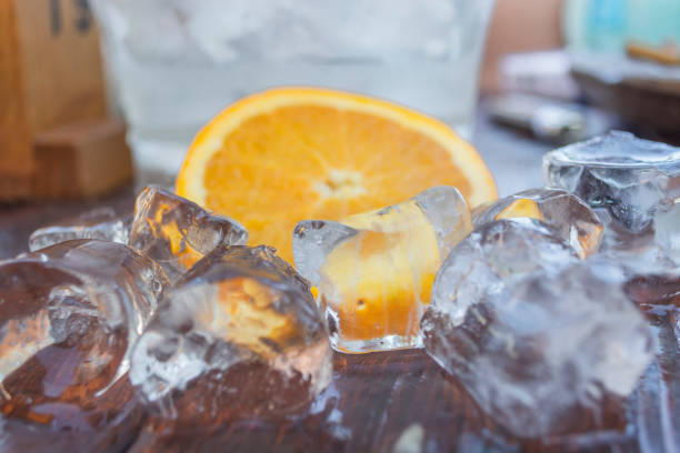 detailed ,close up view of ice cubes on wood table, to defrost, slice of orange on background - defrost stock pictures, royalty-free photos & images