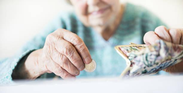 Detaillierte Nahaufnahme Foto von nicht wiederzuerkennenden älteren Frauen Hände zählen verbleibende Münzen aus der Rente in ihrem Portemonnaie nach der Zahlung von Rechnungen. – Foto