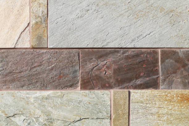 detailed tan brown rust block cut slate rock wall close-up stock photo