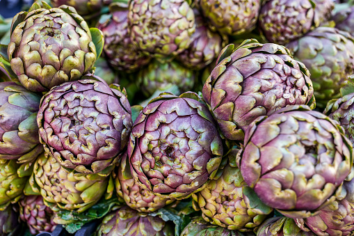 A detailed view of the typical Roman artichokes (Romaneschi) ready to be cooked according to the culinary tradition of Jewish and Roman culture. The traditional Mediterranean diet consists of natural, healthy and fresh products, including fruits, vegetables and grains. Image in high definition format.