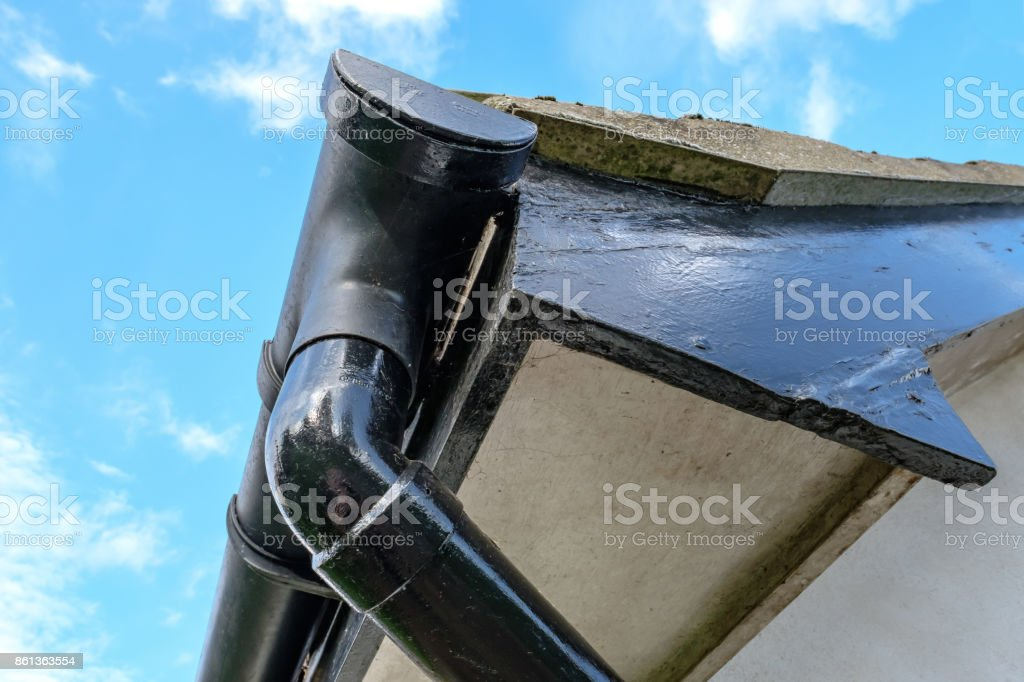 Detailed view of a detached house, showing detail of the guttering, roof line and down-pipe, against a clear sky in the autumn. stock photo