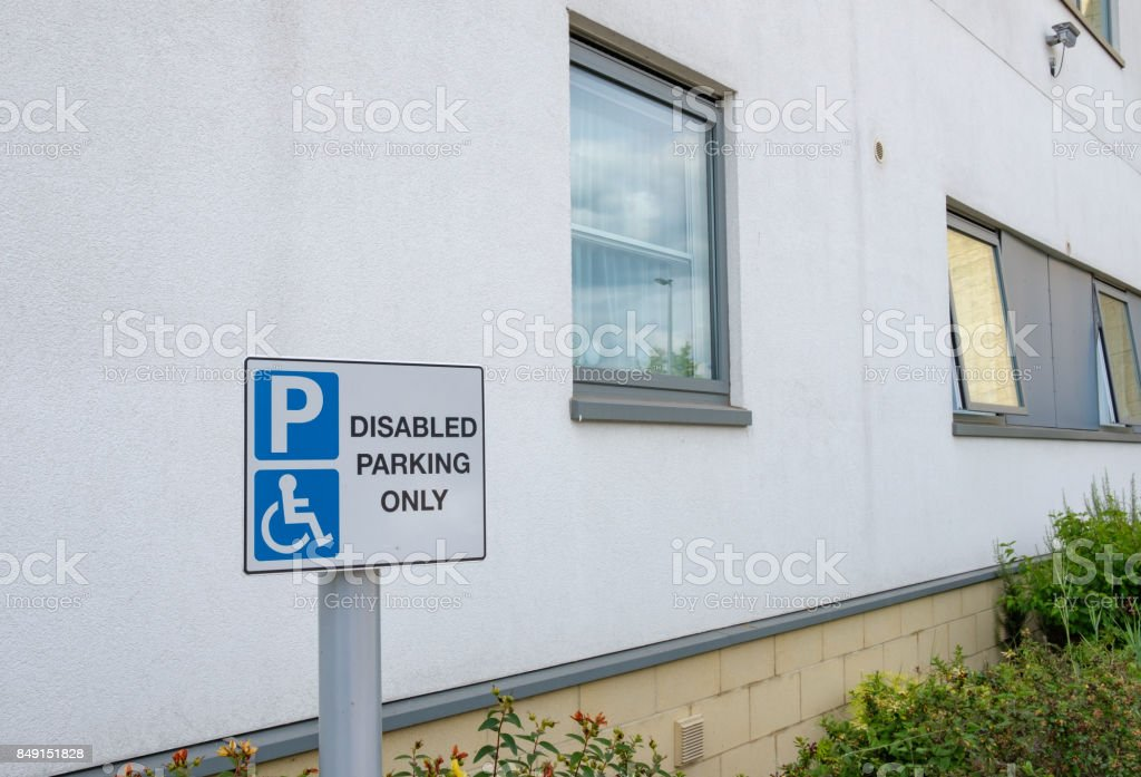Detailed view of a Disabled Parking Sign seen close to the entrance of a large hotel. stock photo