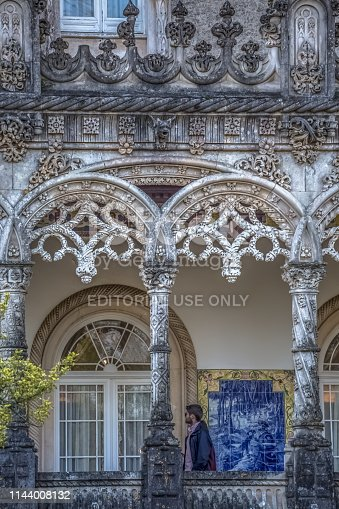 Luso / Aveiro / Portugal - 03 09 2019 : Detailed view of the facade of the Bussaco Palace, with person walking the outside terrace with columns