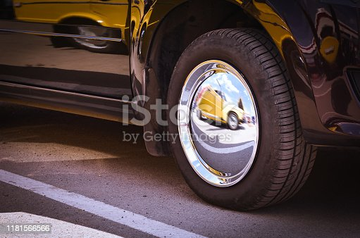 Details of a Dark Shiny Car with Bright Mirror Chrome Wheel Cover and Reflection of another Yellow Car in It.