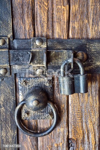 istock details of an old wooden gateway iron lock 1061447354