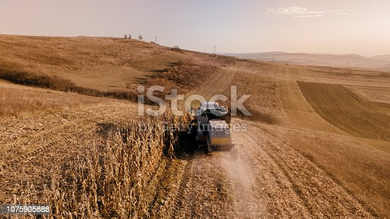 1072634078 istock photo Details of autumn harvest. Aerial view of combine harvesting over the hills 1075905888
