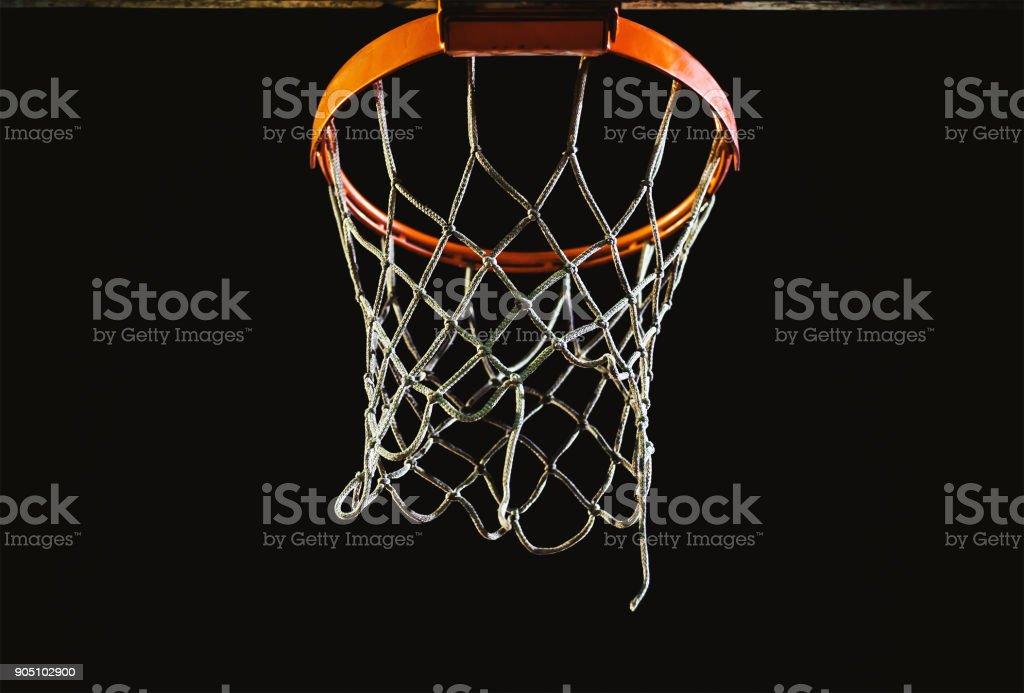 Basketball hoop in dark, illuminated by basketball yard lights.
