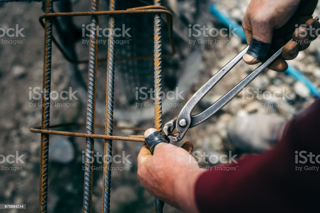 Details of construction worker - hands securing steel bars with wire rod for reinforcement of concrete stock photo