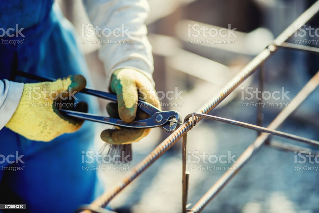 Details of construction workers hands securing steel bars with wire rod for reinforcement of concrete stock photo